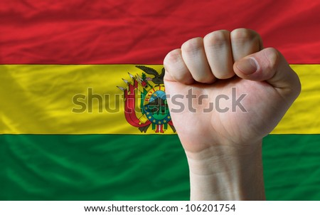 complete national flag of bolivia covers whole frame, waved, crunched and very natural looking. In front plan is clenched fist symbolizing determination - stock photo