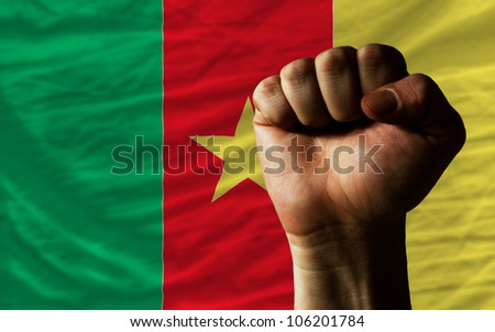 complete national flag of cameroon covers whole frame, waved, crunched and very natural looking. In front plan is clenched fist symbolizing determination - stock photo