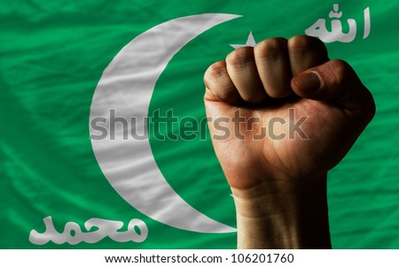 complete national flag of comoros covers whole frame, waved, crunched and very natural looking. In front plan is clenched fist symbolizing determination - stock photo