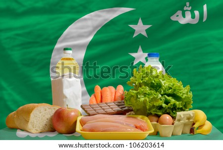complete national flag of comoros covers whole frame, waved, crunched and very natural looking. In front plan are fundamental food ingredients for consumers, symbolizing consumerism - stock photo