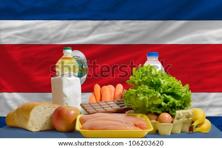 complete national flag of costa rica covers whole frame, waved, crunched and very natural looking. In front plan are fundamental food ingredients for consumers, symbolizing consumerism - stock photo