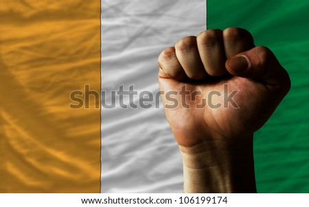 complete national flag of cote'd ivore covers whole frame, waved, crunched and very natural looking. In front plan is clenched fist symbolizing determination - stock photo
