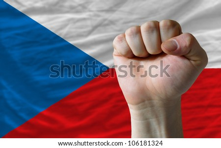complete national flag of czech covers whole frame, waved, crunched and very natural looking. In front plan is clenched fist symbolizing determination - stock photo