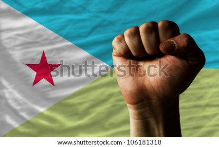 complete national flag of djibouti covers whole frame, waved, crunched and very natural looking. In front plan is clenched fist symbolizing determination - stock photo