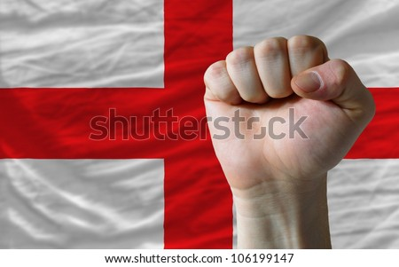complete national flag of england covers whole frame, waved, crunched and very natural looking. In front plan is clenched fist symbolizing determination