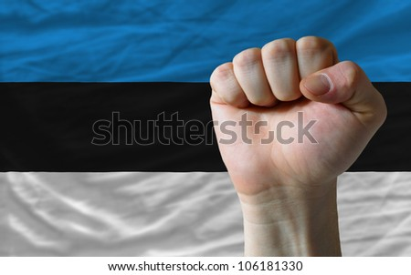 complete national flag of estonia covers whole frame, waved, crunched and very natural looking. In front plan is clenched fist symbolizing determination - stock photo