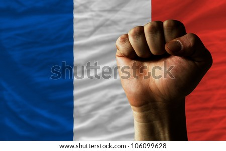 complete national flag of france covers whole frame, waved, crunched and very natural looking. In front plan is clenched fist symbolizing determination - stock photo