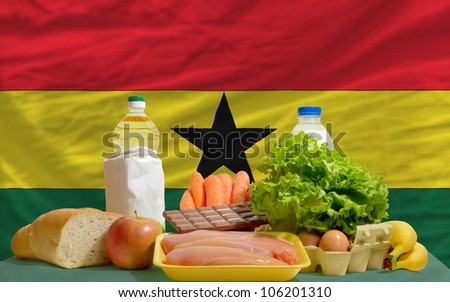 complete national flag of ghana covers whole frame, waved, crunched and very natural looking. In front plan are fundamental food ingredients for consumers, symbolizing consumerism - stock photo