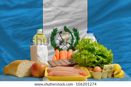 complete national flag of guatemala covers whole frame, waved, crunched and very natural looking. In front plan are fundamental food ingredients for consumers, symbolizing consumerism - stock photo