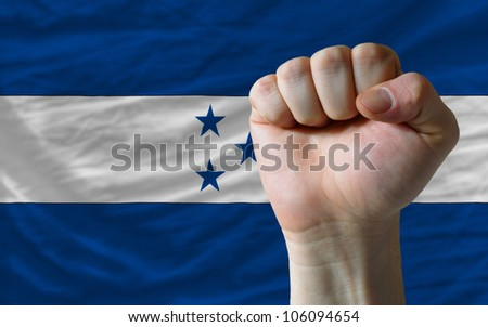 complete national flag of honduras covers whole frame, waved, crunched and very natural looking. In front plan is clenched fist symbolizing determination - stock photo