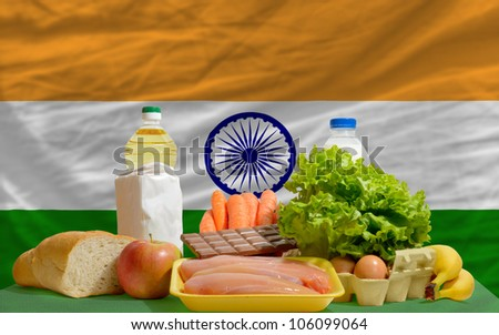 complete national flag of india covers whole frame, waved, crunched and very natural looking. In front plan are fundamental food ingredients for consumers, symbolizing consumerism - stock photo