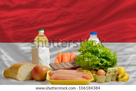 complete national flag of indonesia covers whole frame, waved, crunched and very natural looking. In front plan are fundamental food ingredients for consumers, symbolizing consumerism - stock photo