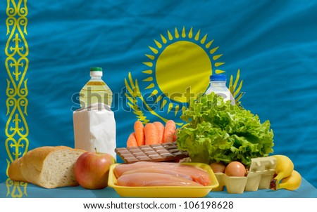 complete national flag of kazakhstan covers whole frame, waved, crunched and very natural looking. In front plan are fundamental food ingredients for consumers, symbolizing consumerism - stock photo