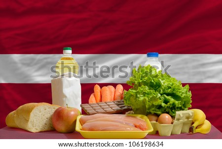 complete national flag of latvia covers whole frame, waved, crunched and very natural looking. In front plan are fundamental food ingredients for consumers, symbolizing consumerism - stock photo