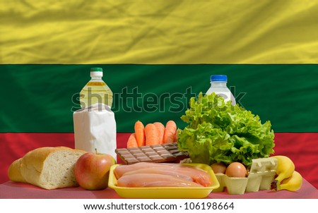 complete national flag of lithuania covers whole frame, waved, crunched and very natural looking. In front plan are fundamental food ingredients for consumers, symbolizing consumerism - stock photo