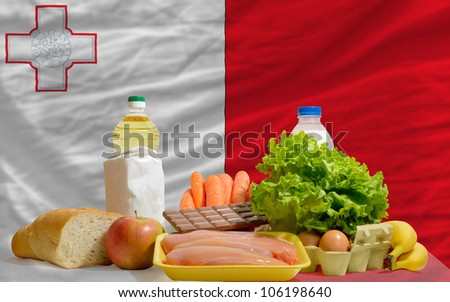 complete national flag of malta covers whole frame, waved, crunched and very natural looking. In front plan are fundamental food ingredients for consumers, symbolizing consumerism - stock photo