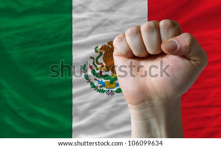 complete national flag of mexico covers whole frame, waved, crunched and very natural looking. In front plan is clenched fist symbolizing determination - stock photo