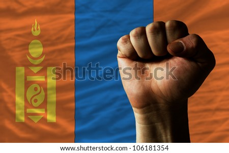 complete national flag of mongolia covers whole frame, waved, crunched and very natural looking. In front plan is clenched fist symbolizing determination - stock photo
