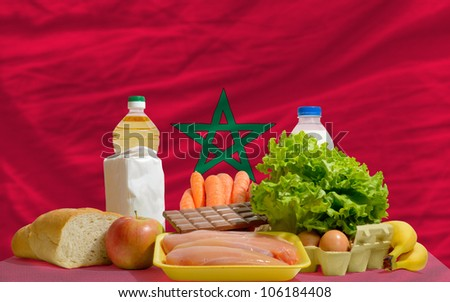 complete national flag of morocco covers whole frame, waved, crunched and very natural looking. In front plan are fundamental food ingredients for consumers, symbolizing consumerism - stock photo