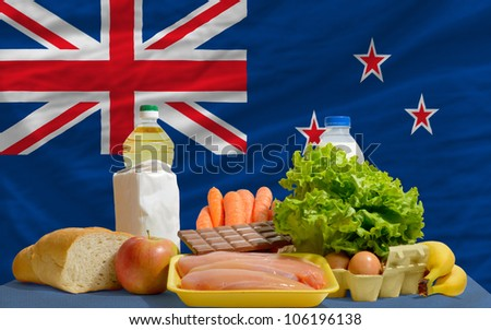 complete national flag of new zealand covers whole frame, waved, crunched and very natural looking. In front plan are fundamental food ingredients for consumers, symbolizing consumerism - stock photo