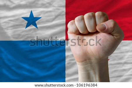 complete national flag of panama covers whole frame, waved, crunched and very natural looking. In front plan is clenched fist symbolizing determination - stock photo