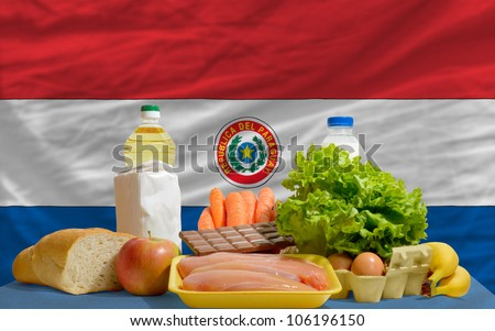 complete national flag of paraguay covers whole frame, waved, crunched and very natural looking. In front plan are fundamental food ingredients for consumers, symbolizing consumerism - stock photo