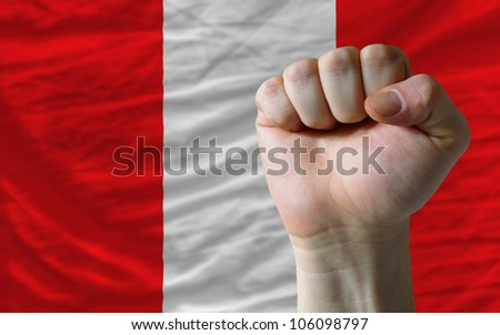 complete national flag of peru covers whole frame, waved, crunched and very natural looking. In front plan is clenched fist symbolizing determination