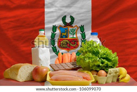 complete national flag of peru covers whole frame, waved, crunched and very natural looking. In front plan are fundamental food ingredients for consumers, symbolizing consumerism - stock photo