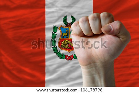 complete national flag of peru covers whole frame, waved, crunched and very natural looking. In front plan is clenched fist symbolizing determination - stock photo