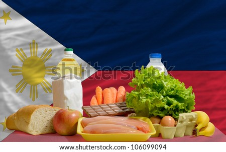 complete national flag of philippines covers whole frame, waved, crunched and very natural looking. In front plan are fundamental food ingredients for consumers, symbolizing consumerism - stock photo