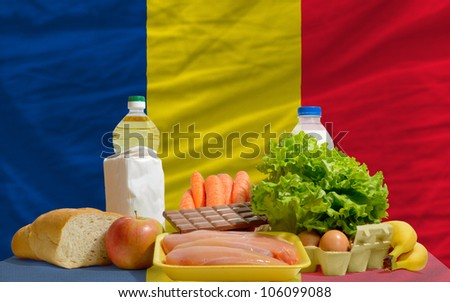 complete national flag of romania covers whole frame, waved, crunched and very natural looking. In front plan are fundamental food ingredients for consumers, symbolizing consumerism an human needs - stock photo