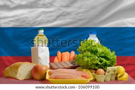 complete national flag of russia covers whole frame, waved, crunched and very natural looking. In front plan are fundamental food ingredients for consumers, symbolizing consumerism an human needs - stock photo