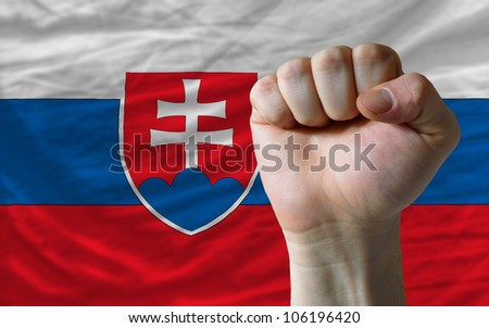 complete national flag of slovakia covers whole frame, waved, crunched and very natural looking. In front plan is clenched fist symbolizing determination - stock photo