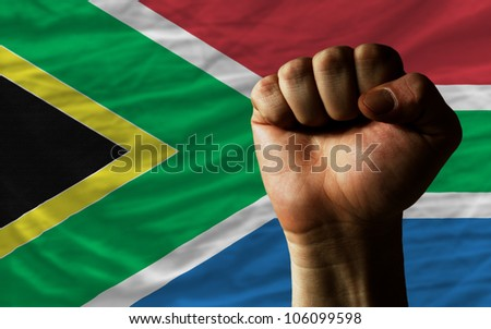 complete national flag of south africa covers whole frame, waved, crunched and very natural looking. In front plan is clenched fist symbolizing determination - stock photo