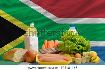 complete national flag of south africa covers whole frame, waved, crunched and very natural looking. In front plan are fundamental food ingredients for consumers, symbolizing consumerism - stock photo