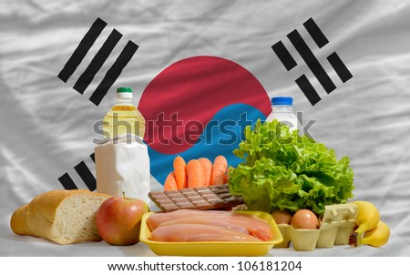 complete national flag of south korea covers whole frame, waved, crunched and very natural looking. In front plan are fundamental food ingredients for consumers, symbolizing consumerism - stock photo