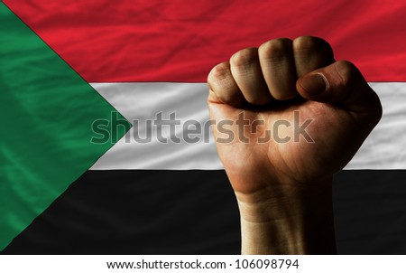complete national flag of sudan covers whole frame, waved, crunched and very natural looking. In front plan is clenched fist symbolizing determination - stock photo