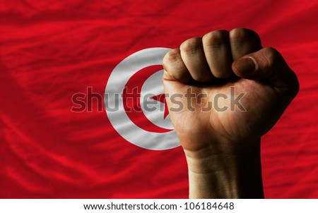 complete national flag of tunisia covers whole frame, waved, crunched and very natural looking. In front plan is clenched fist symbolizing determination - stock photo