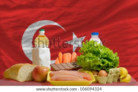 complete national flag of turkey covers whole frame, waved, crunched and very natural looking. In front plan are fundamental food ingredients for consumers, symbolizing consumerism an human needs - stock photo