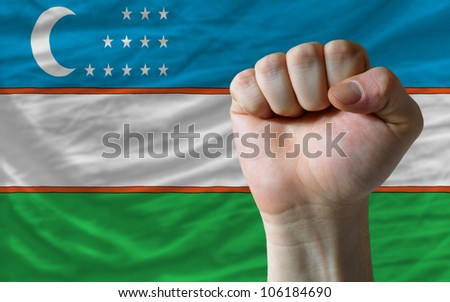 complete national flag of uzbekistan covers whole frame, waved, crunched and very natural looking. In front plan is clenched fist symbolizing determination - stock photo