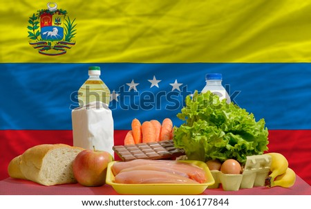 complete national flag of venezuela covers whole frame, waved, crunched and very natural looking. In front plan are fundamental food ingredients for consumers, symbolizing consumerism - stock photo
