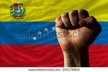 complete national flag of venezuela covers whole frame, waved, crunched and very natural looking. In front plan is clenched fist symbolizing determination - stock photo