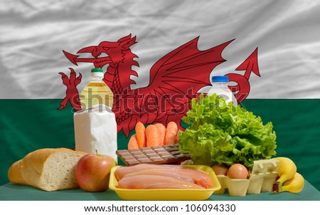 complete national flag of wales covers whole frame, waved, crunched and very natural looking. In front plan are fundamental food ingredients for consumers, symbolizing consumerism an human needs - stock photo