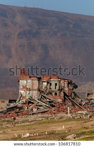 Completely destroyed a two-story brick building on the background of the mountains. - stock photo