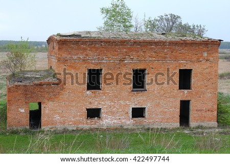 Completely destroyed brick building, overgrown with greens and bushes on a roof. - stock photo