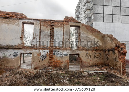 Completely destroyed two-storey brick house with holes for windows. Abandoned house destroyed city of dampness and dirt. Demolition of houses. Background urban ruins to crisis of design. trash design - stock photo