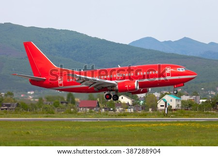 Completely red plane just a seconds before landing at the airport - stock photo