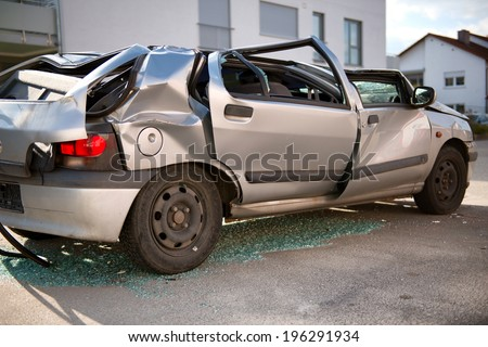 Completely wrecked silver hatchback sedan car with a flattened roof, shattered windows and buckled coachwork standing upright in the road surrounded by shattered glass shards following an accident - stock photo