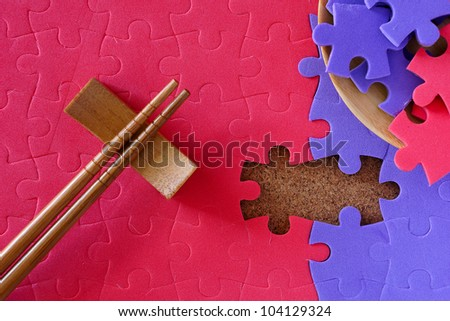 Completing the missing jigsaw puzzle concept, with chopstick for business concept - stock photo