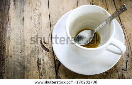 Completion of the coffee. Closeup empty cofee cup on wooden floor. - stock photo
